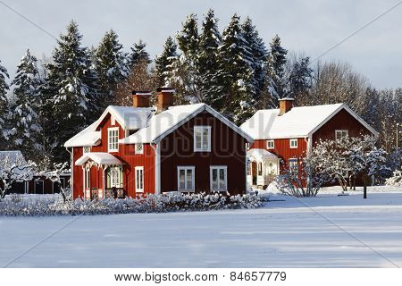 old red farm, cottages set in a rural winter landscape