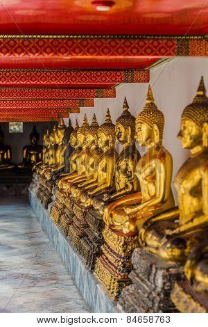 aligned golden buddha statues at Wat Pho temple Bangkok Thailand