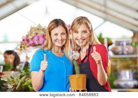 Two happy women with cactus in garden center holding their thumbs up