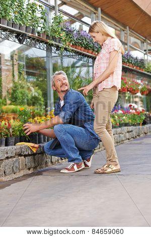 Smiling woman talking to a gardener in a nursery shop