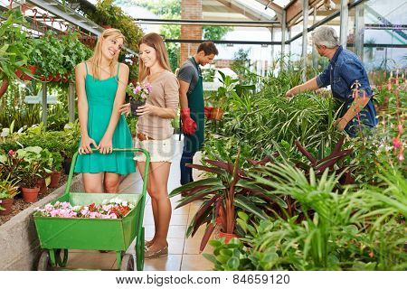 Two happy women buying flowers together in a nursery shop
