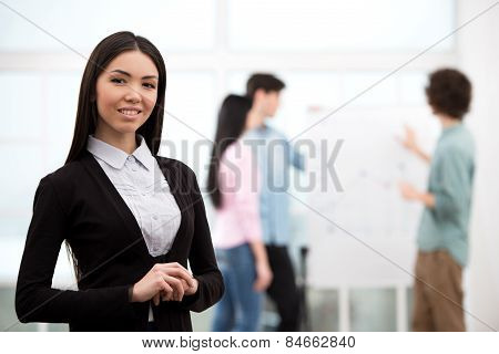 Young businesswoman with her business team on background