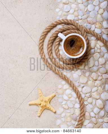 Cup of coffee on the sea pebbles on beach party
