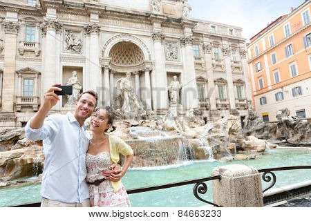 Tourist couple on travel taking selfie photo by Trevi Fountain in Rome, Italy. Happy young romantic couple traveling in Europe taking self-portrait with smartphone camera. Man and woman happy together