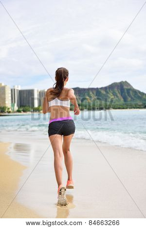 Running exercise - Female runner woman running and jogging on beach run. Athlete fitness runner jogger training living healthy active lifestyle exercising on Waikiki Beach, Honolulu, Oahu, Hawaii, USA