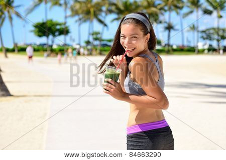 Green detox cleanse vegetable smoothie woman. Healthy sport woman runner drinking fresh and happy after running. Fitness and healthy lifestyle concept with multicultural Asian Caucasian female model.