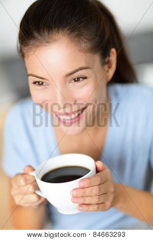 Asian chinese woman drinking coffee or black tea. Portrait of young adult student smiling holding mug at cafe or home in the morning as part of a healthy breakfast.