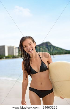 Surfer girl surfing walking with surfboard on Waikiki Beach, Oahu, Hawaii. Female bikini woman walking with surfboard living healthy active lifestyle on Hawaiian beach. Asian Caucasian model.
