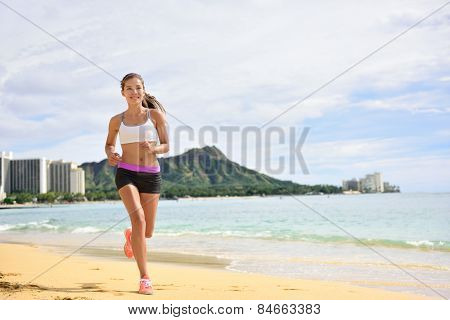 Sport running fitness woman jogging on beach run. Female athlete runner jogger training living healthy active exercise lifestyle exercising outdoor on Waikiki Beach, Honolulu, Oahu, Hawaii, USA.