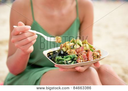 Poke bowl salad plate. A traditional local Hawaii food dish with raw marinated ahi yellowfin tuna fish. Woman sitting on beach eating lunch.