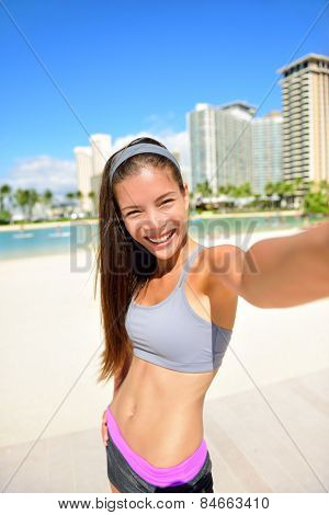 Fitness selfie woman self portrait after workout. Sport athlete taking selfies photo after working out running and training outdoors on beach. Fit female Asian Caucasian sport model smiling happy.