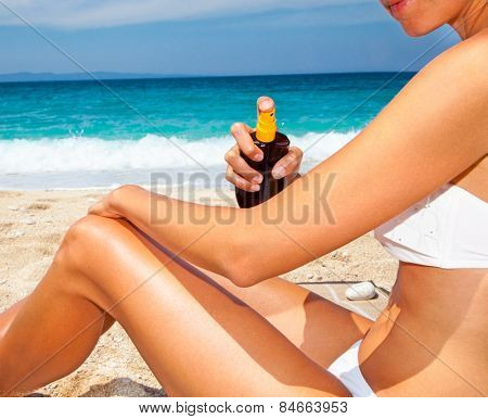 Woman applying suntan lotion from a spray bottle . Greece.
