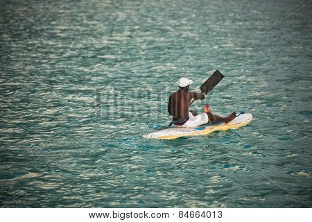 Young Seychellois Man On A Surfboard In The Ocean