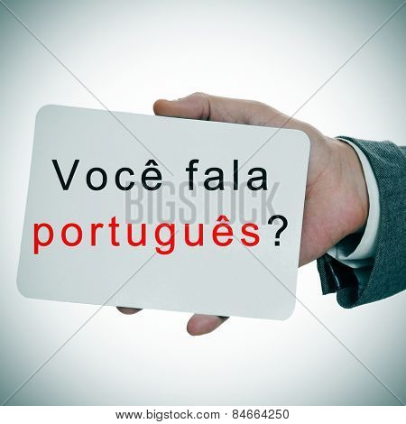 man hands showing a signboard with the sentence voce fala portugues? do you speak portuguese written in it