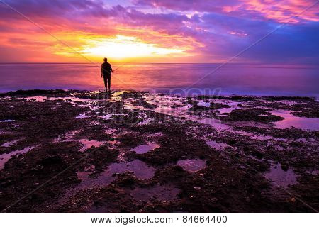 Silhouette of fisherman in amazing colorful sunset light, enjoying angling on beautiful coastline, recreation outdoors, favorite men's sport