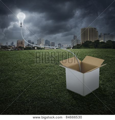 Glowing Light Bulb Float Over Box On City, Think Outside The Box Concept