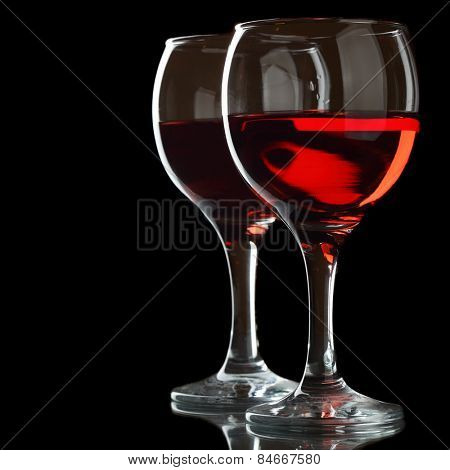 Two glasses of red wine isolated over black background