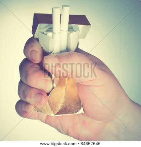Man's hand crushing cigarette box. Retro style filtred image