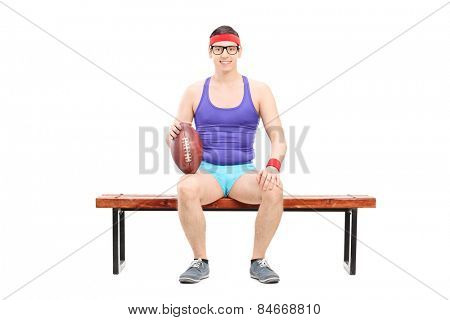 Male football player sitting on a bench isolated on white background