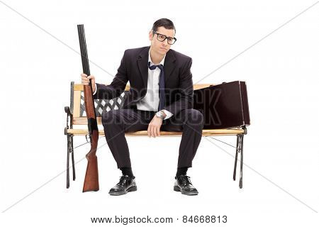 Upset businessman holding a rifle seated on a bench isolated on white background