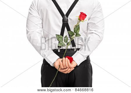 Close-up on a man holding flower and a red box behind his back isolated on white background