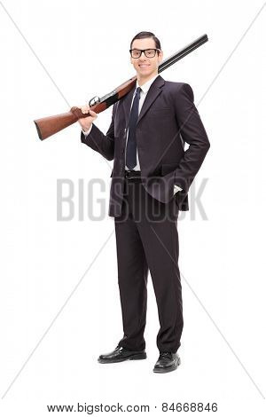 Full length portrait of a businessman holding a rifle over his shoulder isolated on white background