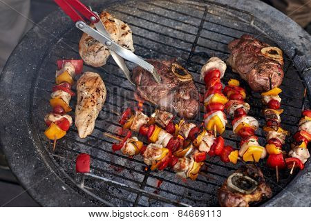 tasty meat and skewers on the barbecue outdoors