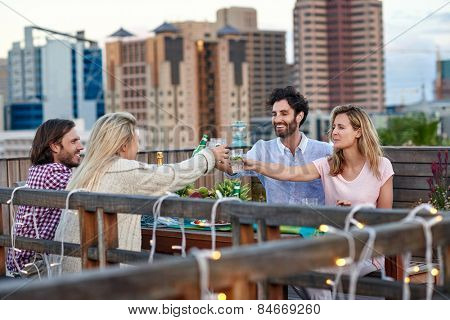 Group of friends making a toast with drinks while hanging out outdoors on the rooftop