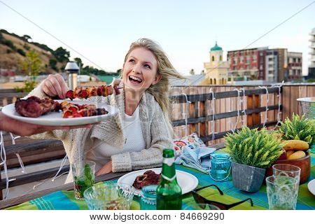 Man serves woman skewer kebabs at outdoor rooftop barbeque dinner party