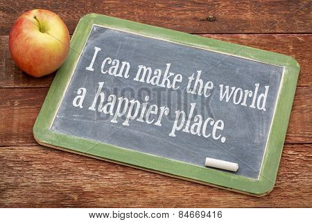 I can make the world a happier place - positive words on a slate blackboard against red barn wood