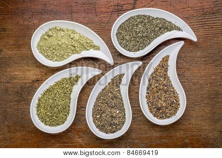 teardrop shaped bowls of seaweed diet supplements (bladderwrack, sea lettuce, kelp, wakame and Irish moss) on a grunge wood background