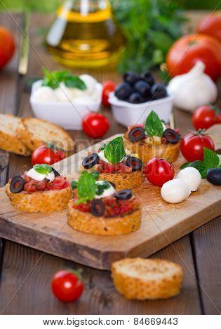 Bruschetta with mozzarella on chopping board