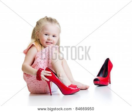 Little girl trying on mummy's shoes
