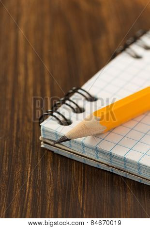 pencil and checked notebook on wooden background
