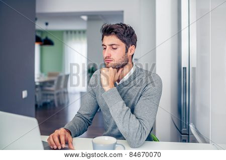 Handsome young concentrated businessman working from home with a laptop with his coffee mug