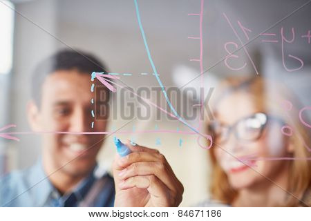 Businessman sketching graph on transparent board with highlighter