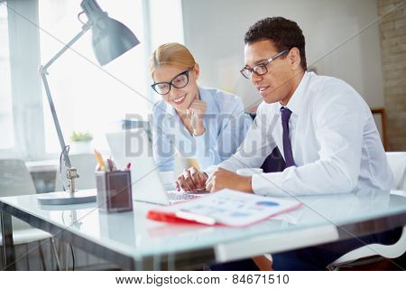 Charming secretary and her boss browsing data for new project at meeting