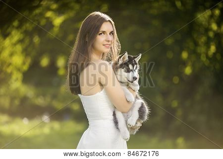 Girl In A White Dress Holding A Puppy Husky