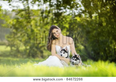 Girl In White Dress Sitting On The Grass And Hugging Two Husky Puppies