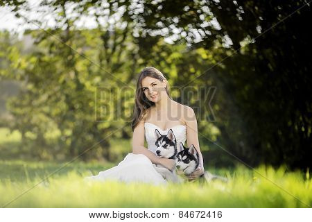 The Girl In The White Dress Smiles. Sitting On The Grass And Hugging Two Husky Puppies