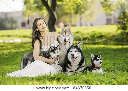 ..the Girl In The White Dress Smiles. Sitting On The Grass And Hugging Family Dogs Husky. Summer