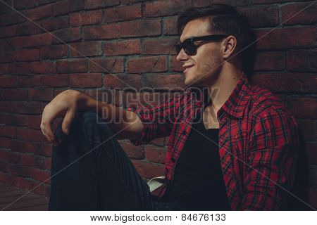 portrait hipster smilling man with glasses casual clothes unbuttoned shirt sitting and leaning at th