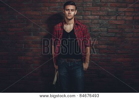 Hipster serious man casual clothes unbuttoned shirt and denim jeans standing near brick wall hand in