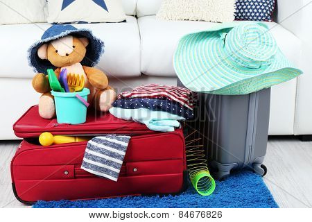 Suitcase packed with clothes and child toys on fur rug and white sofa background