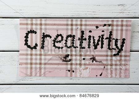 Word creativity written on paper on wooden background