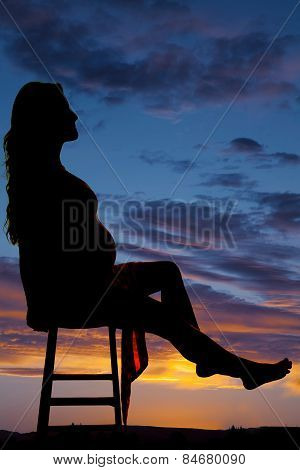 Silhouette Of A Pregnant Woman Sitting Leg Out