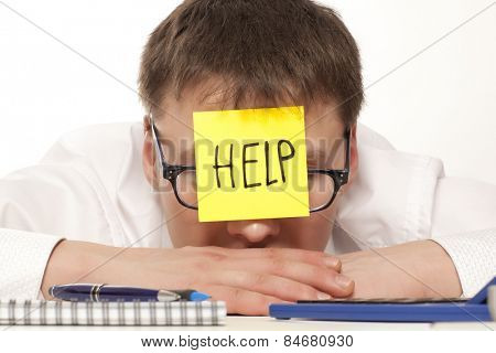 Frustrated young man in formal wear with adhesive note on his forehead leaning his head at the table