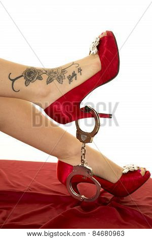 Woman Legs With Tattoo And Red Shoes Handcuffs
