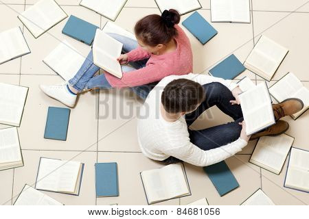 Young woman and man reading a book, top view. Blurred text is unreadable