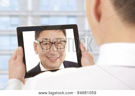 Cropped image of asian businessman attending video conference with colleague on digital tablet